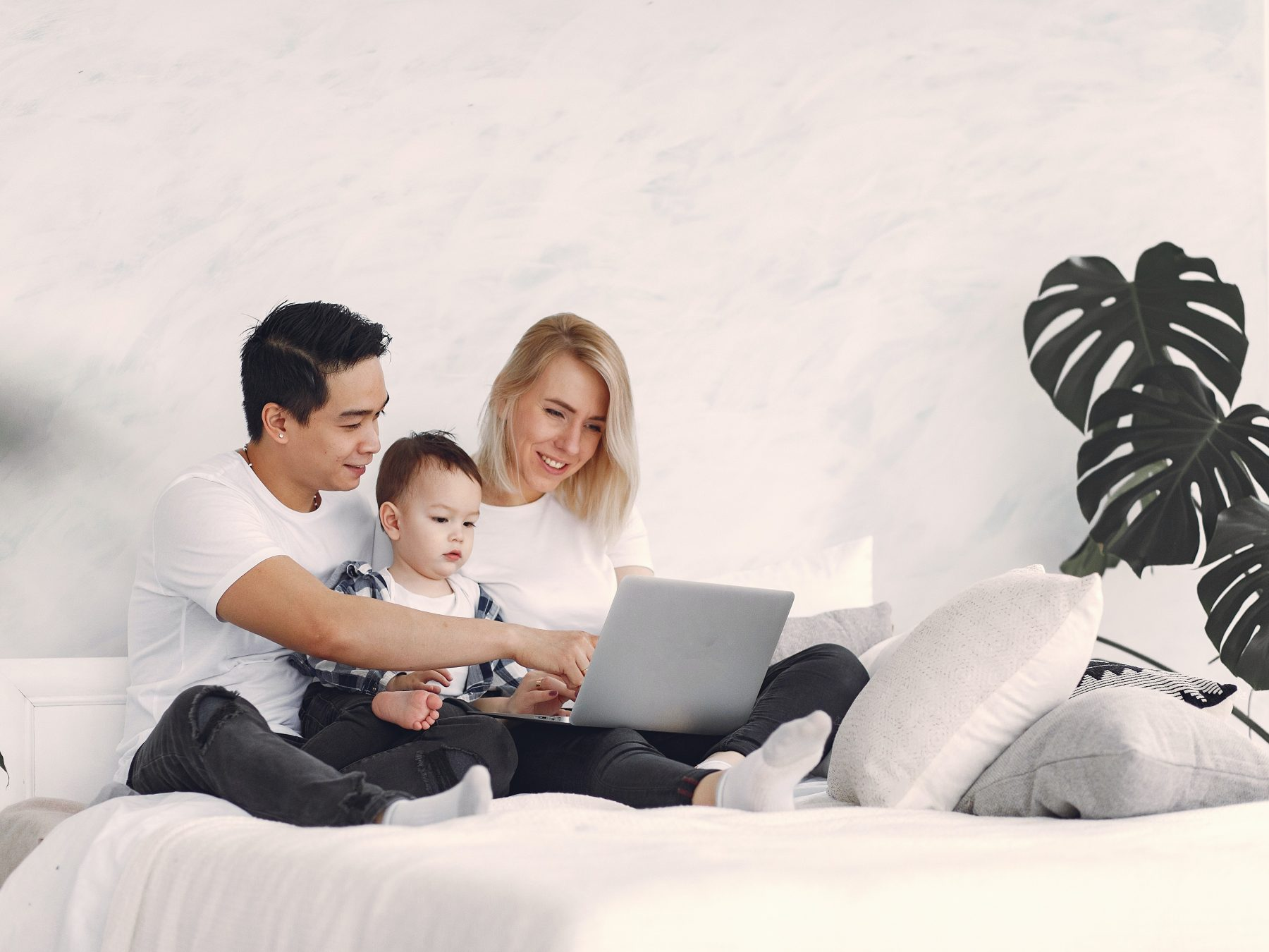 Man and woman sitting on the bed with their child 3912386
